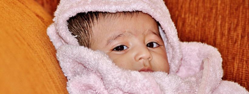 Baby nach dem Baden in Handtuch eingewickelt